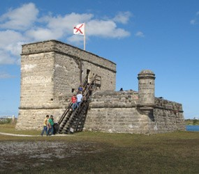 People climbing ladder set against battlement to reach upper level of gray stone Fort Matanzas National Monument